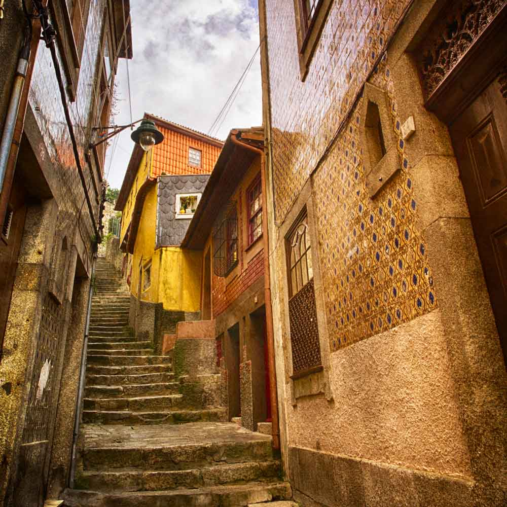 HDR colour image of a pedestrian laneway in Porto, looking up steep steps with terrace houses on either side